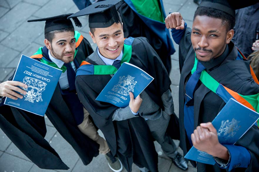 graduates holding ceremony programmes and certificates