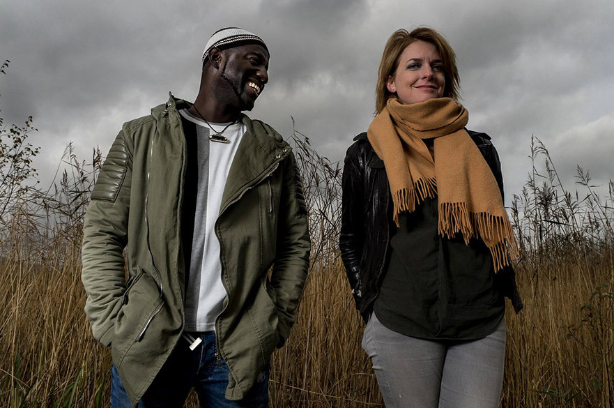 Catrin Finch and Seckou Keita stood together in a field.