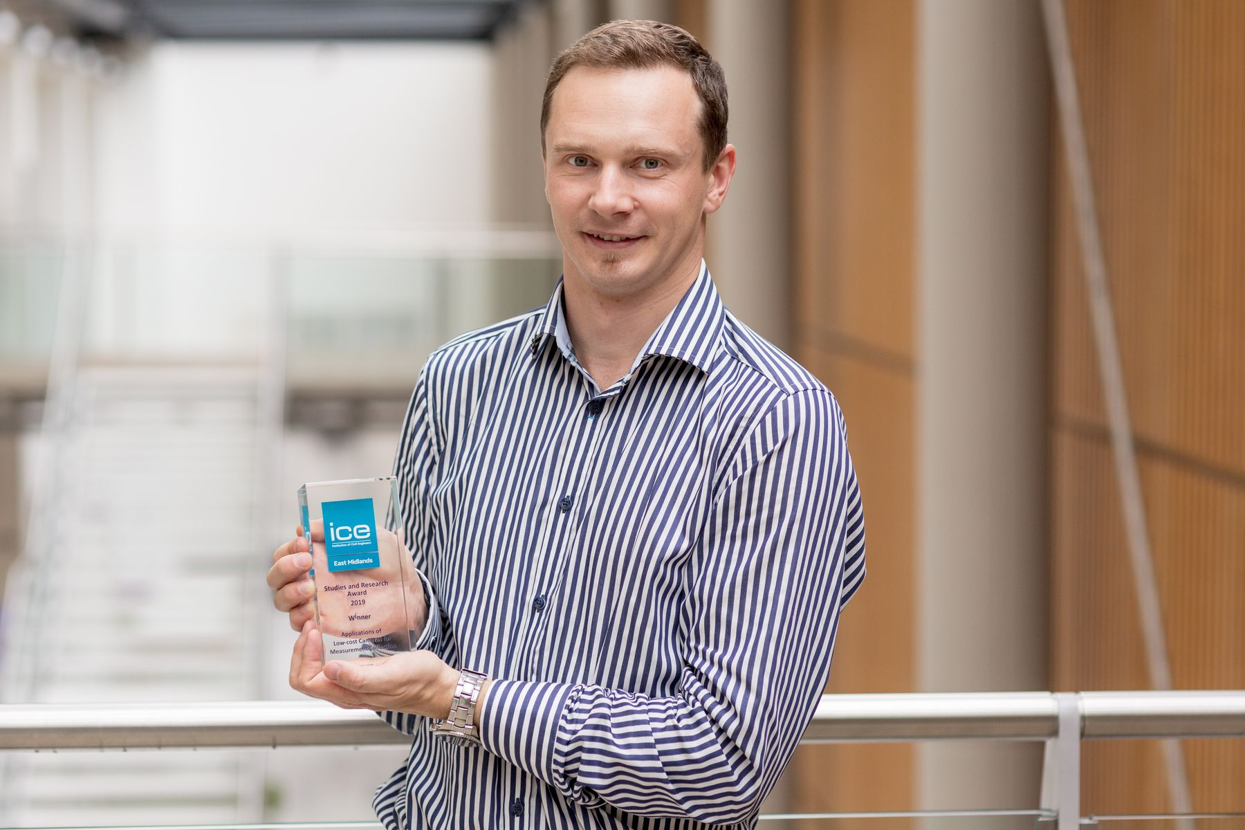 Professor Rolands holding ICE award