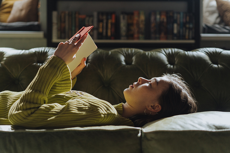 A women laid on a sofa reading a book.