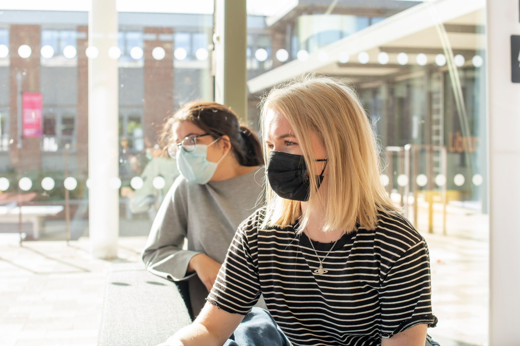 Two students sat at a table wearing face coverings