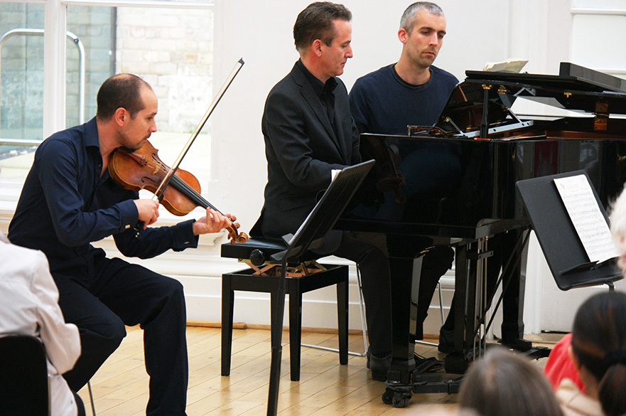 A male violinist and pianist playing in front of an audience.