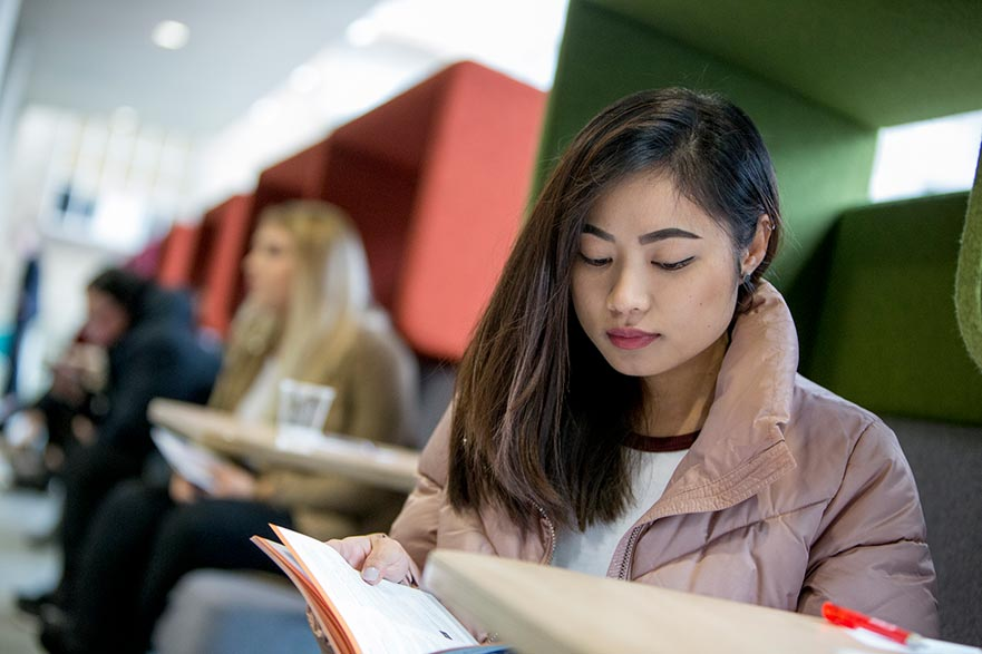 Student reading postgraduate course guide