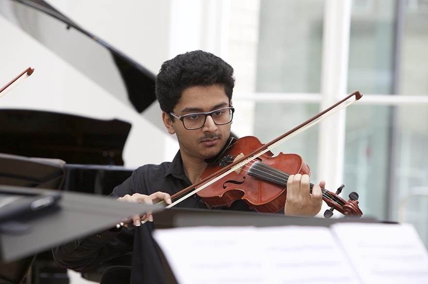 A male student playing a violin.