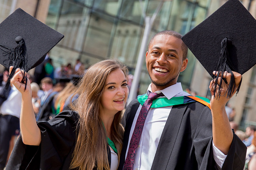 2 graduates holding caps