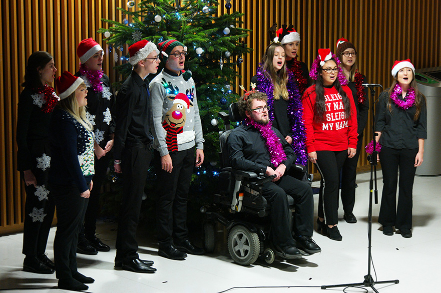 Male and female singers in Christmas jumpers.