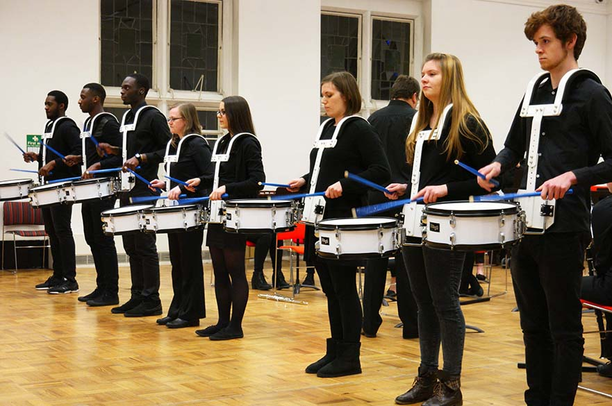 Male and female students performing in a line with snare drums.