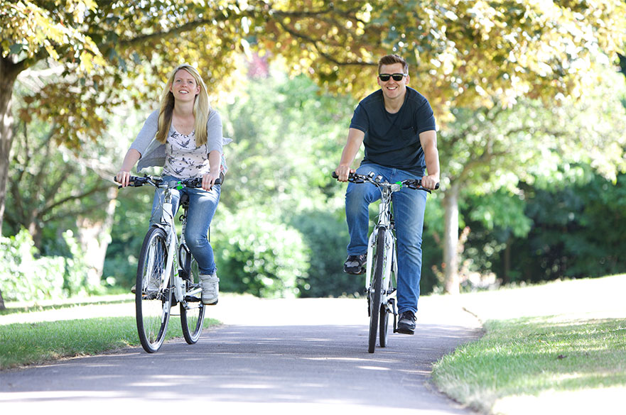Two students cycling through a park