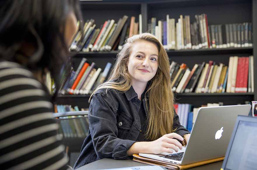Girl sitting down in library with laptop