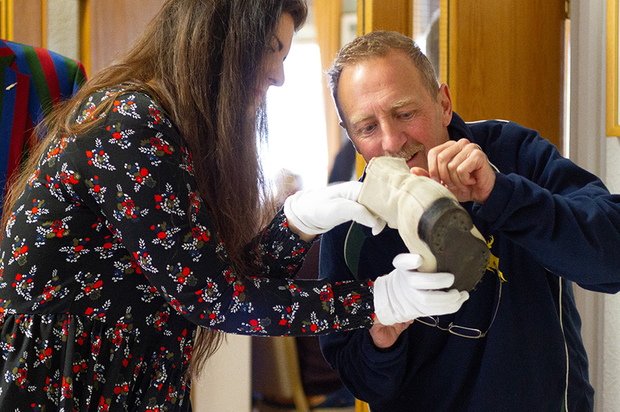Student Eva Sanchez demonstrating the process of cleaning Harold Larwood's boots