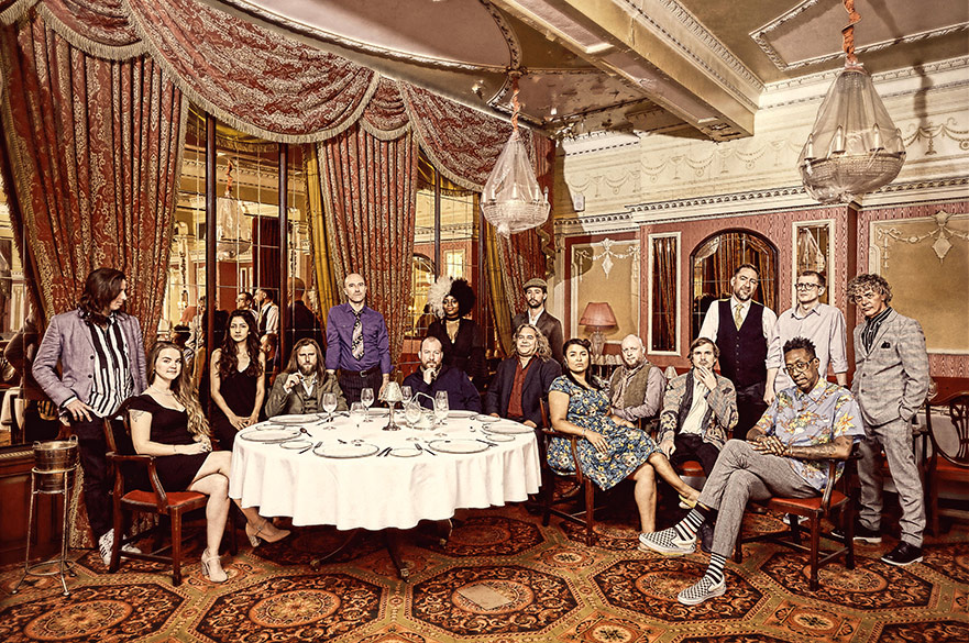 The Invisible Orchestra sat and stood around a table in a grand hotel.