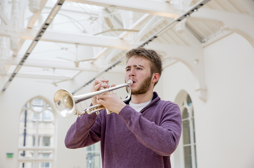 Male student playing a trumpet.