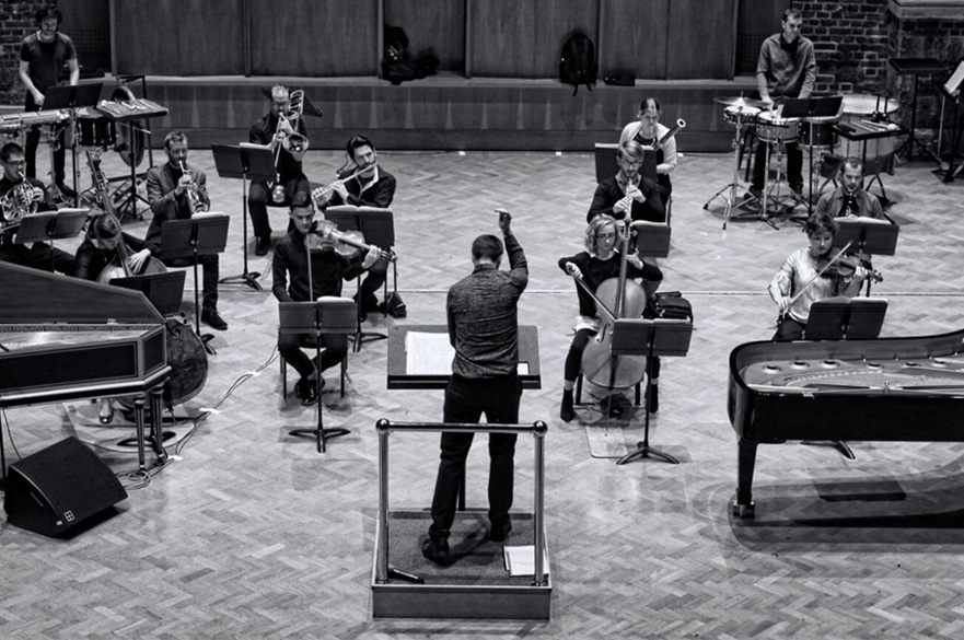 Members of The Riot Ensemble rehearsing in a studio.