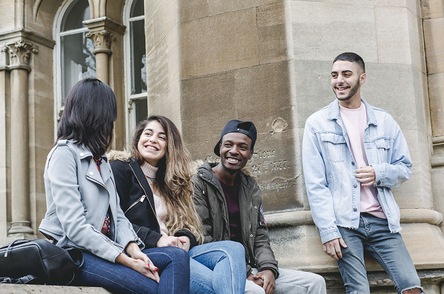 Happy international students sitting on the wall outside Arkwright building