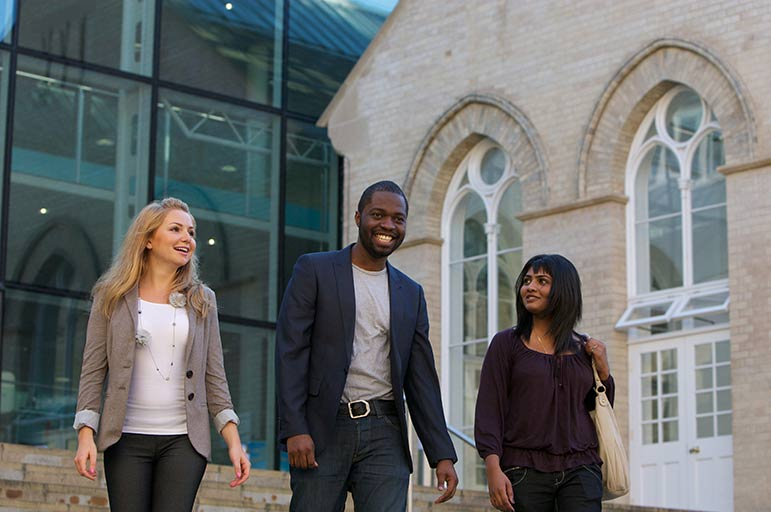 postgraduate students walking together outside the Newton building