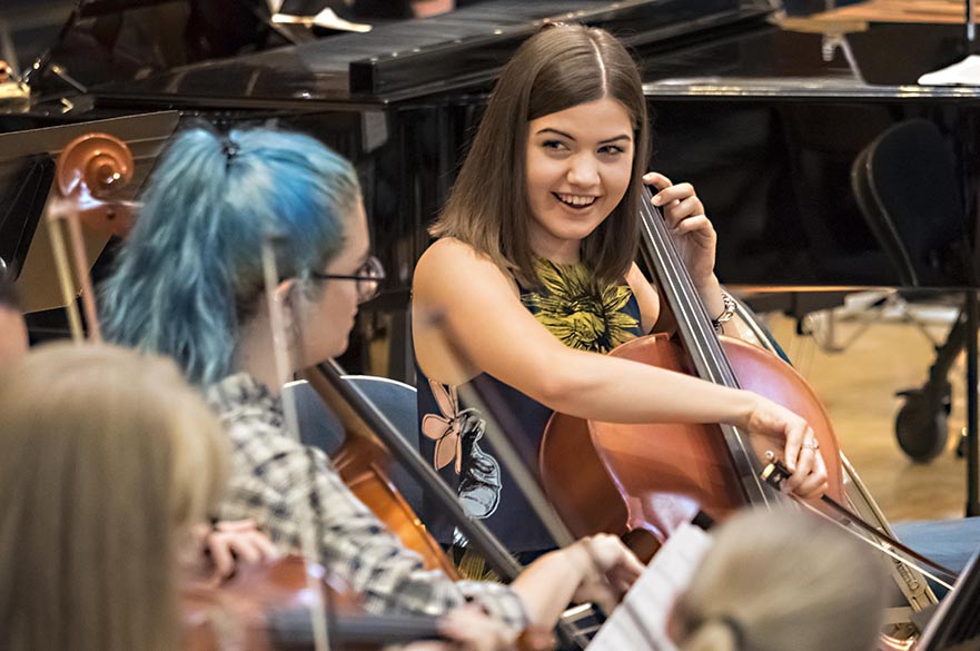 Female students playing the cello in rehearsal.