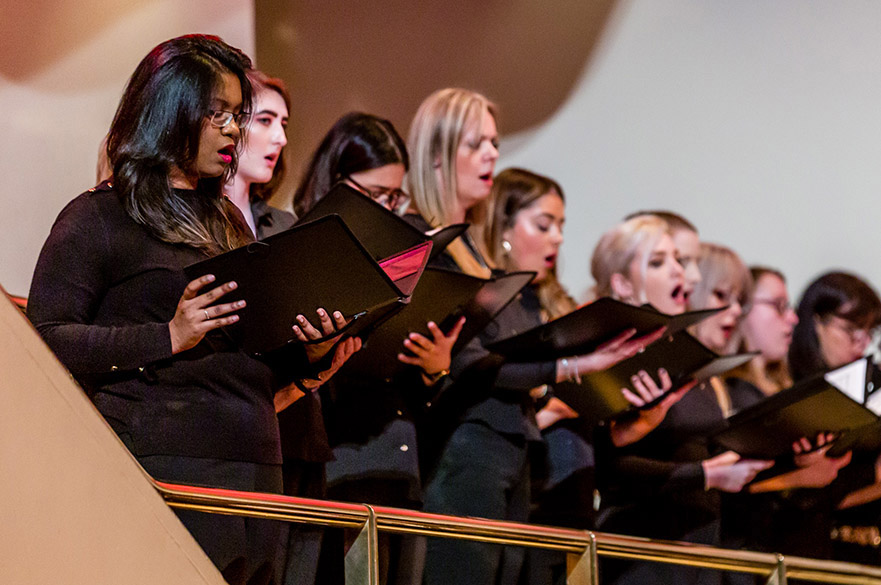 Women singing in a choir on a balcony holding lyric sheets.