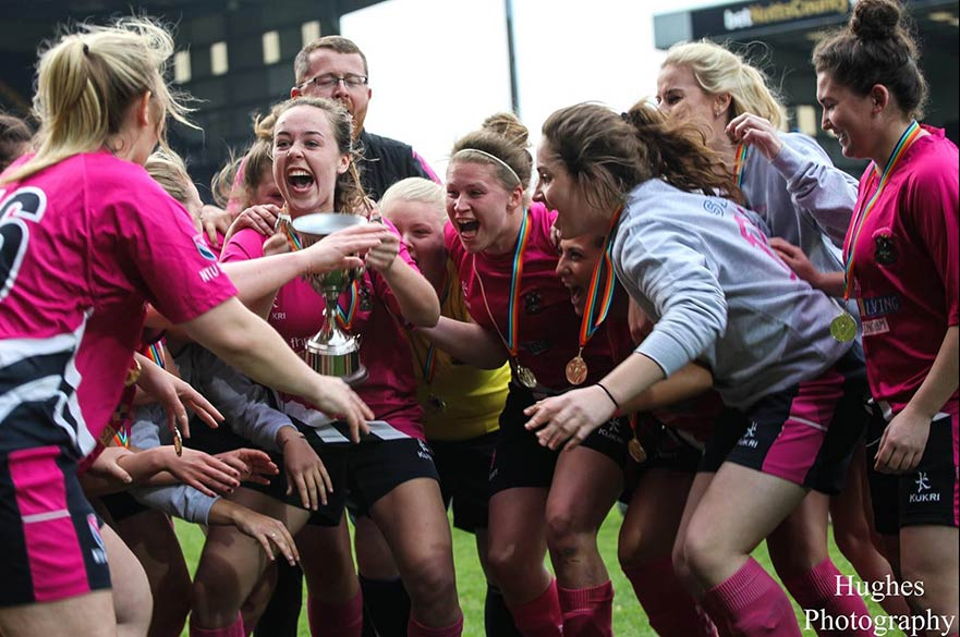 Women's football team celebrating win with trophy
