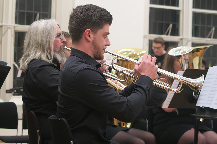 Male students and staff playing trumpets.