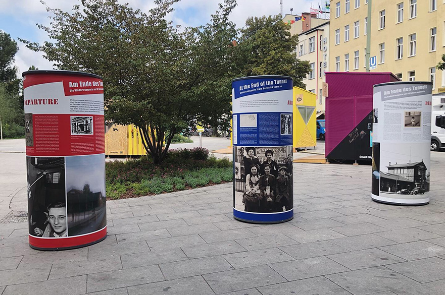 Three circular stands containing text and images about the holocaust on a Berlin street