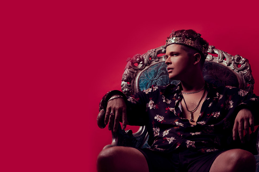 Luke Wright sat on a throne-like chair with a crown on his head.