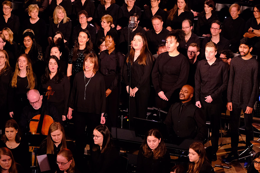 A group of people singing as part of Gospel Choir during a concert.