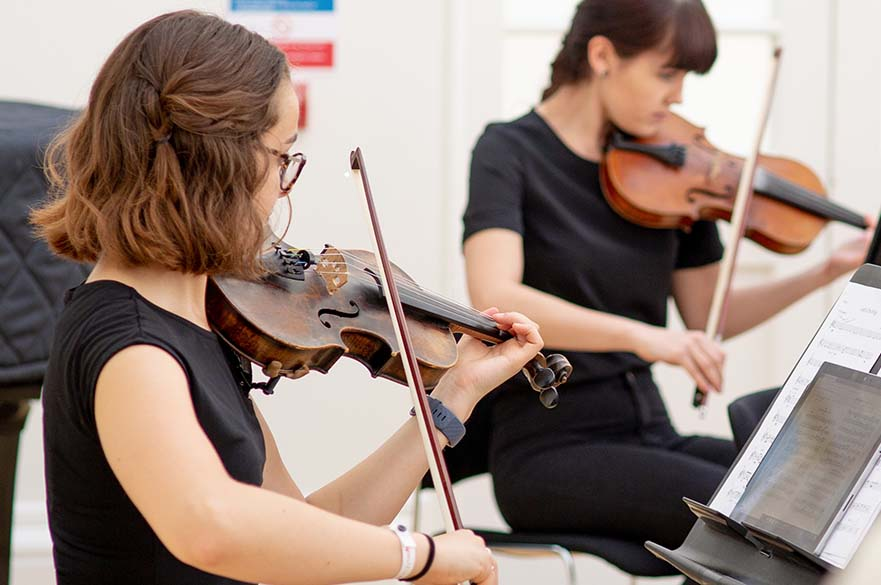 Two female students playing the violin