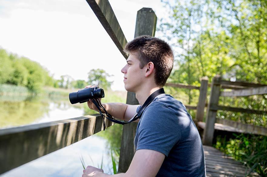 Student using binoculars at Brackenhurst campus