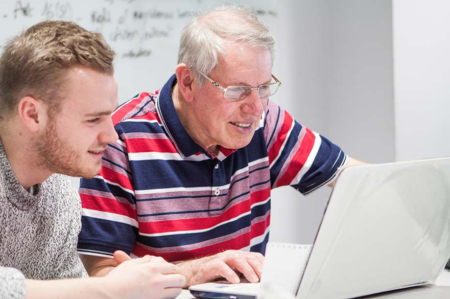 Student and older man working at laptop