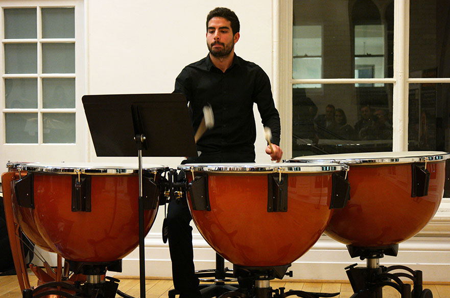 Male playing the timpani drums.