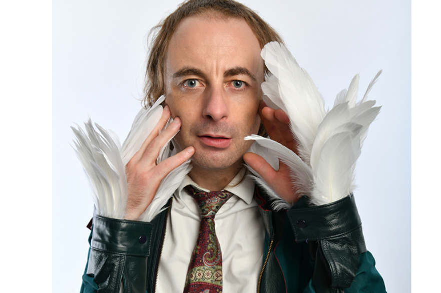 A photo of Paul Foot holding up his hands against his face, with white feathers coming out of his sleeves.