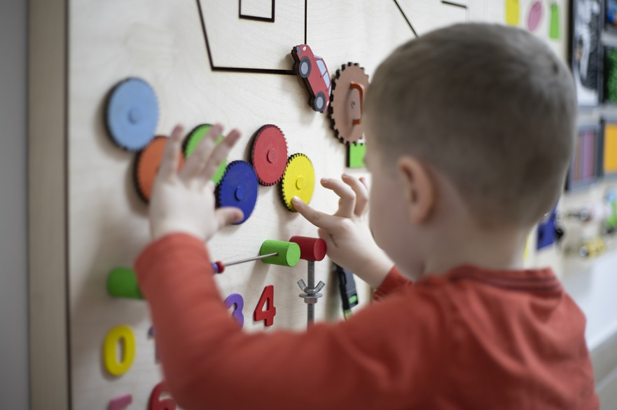 Child playing with a sensory board