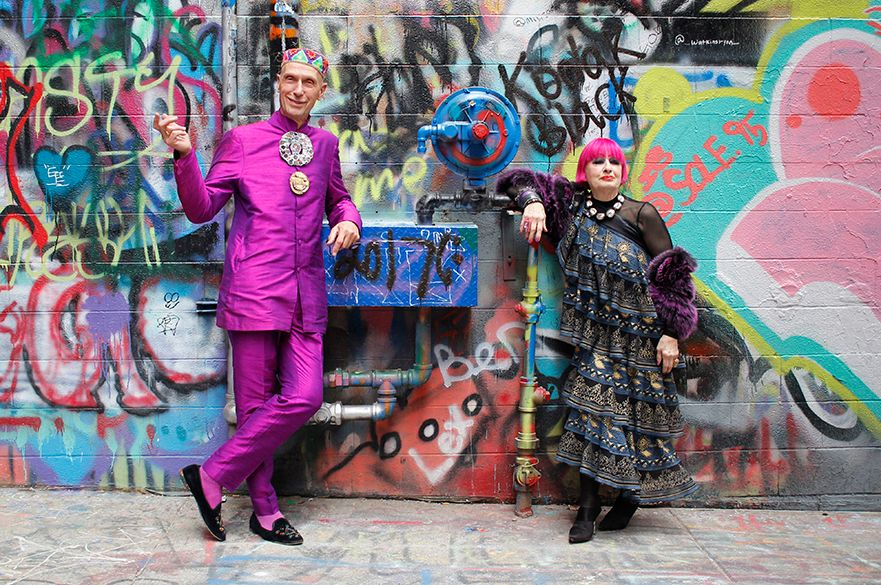 Andrew Logan and Zandra Rhodes stood in front of a wall covered in graffiti.